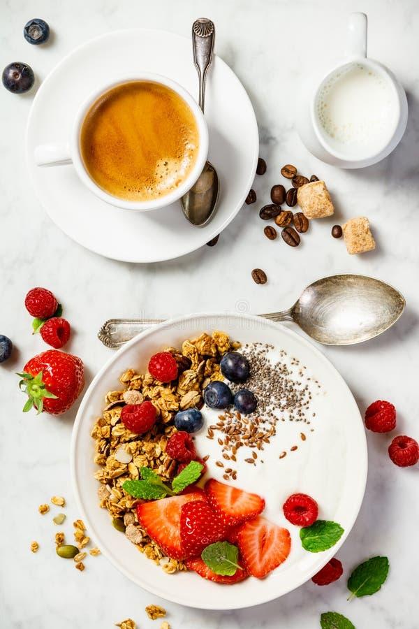健康早餐用咖啡、酸奶、格兰诺拉麦片和莓果 免版税库存照片