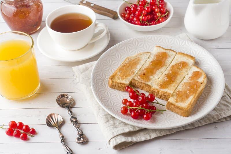 健康早餐用多士、果酱、新鲜的橙汁和红浆果,一杯咖啡在白色桌上的 库存照片
