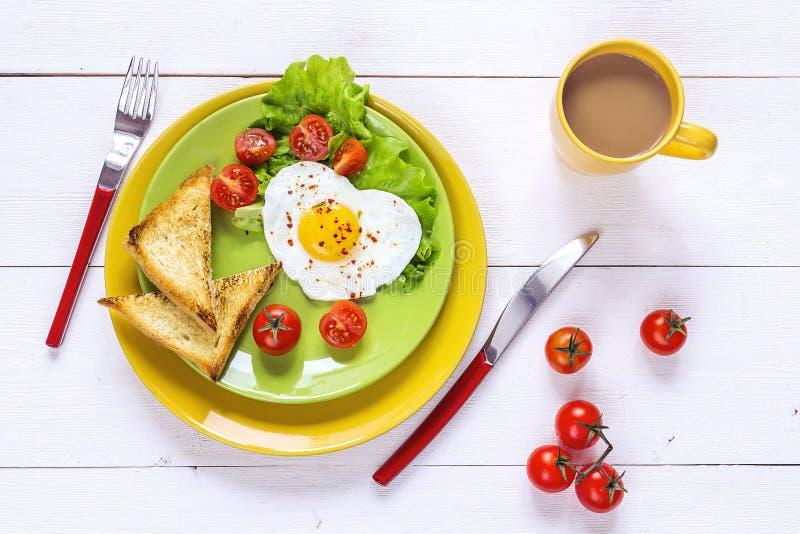 健康早餐用心形的煎蛋,多士,樱桃汤姆 免版税库存图片