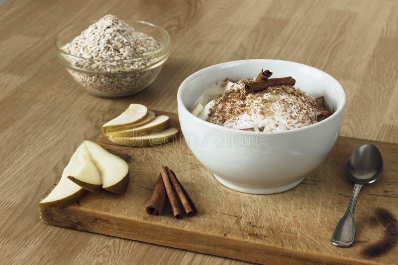 健康早餐用燕麦粥、梨、苹果、椰奶和桂香 免版税库存照片
