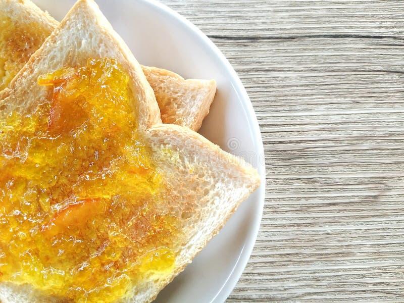 健康早餐用鲜美早餐多士用在木桌上的桔子和菠萝果酱 看法从上面在木桌上 免版税库存照片