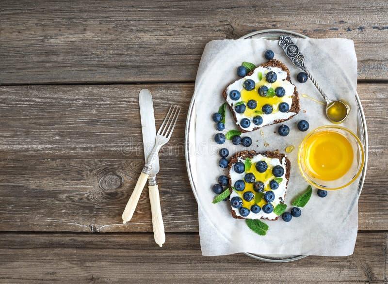 健康早餐设置了与乳清干酪、新鲜的蓝莓和蜂蜜 免版税库存照片