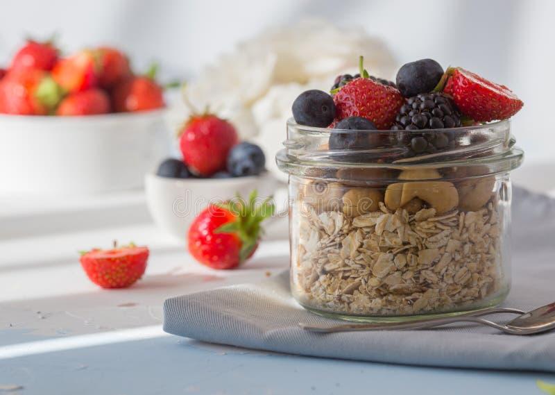 健康早餐超级食物谷物概念用新鲜水果、格兰诺拉麦片、酸奶、坚果和花粉五谷,用食物高在蛋白质, 免版税图库摄影