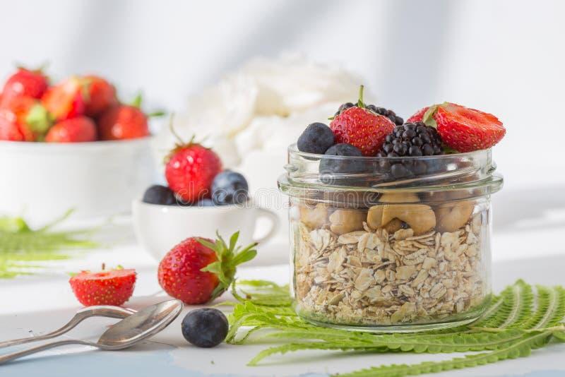 健康早餐超级食物谷物概念用新鲜水果、格兰诺拉麦片、酸奶、坚果和花粉五谷,用食物高在蛋白质, 免版税库存照片