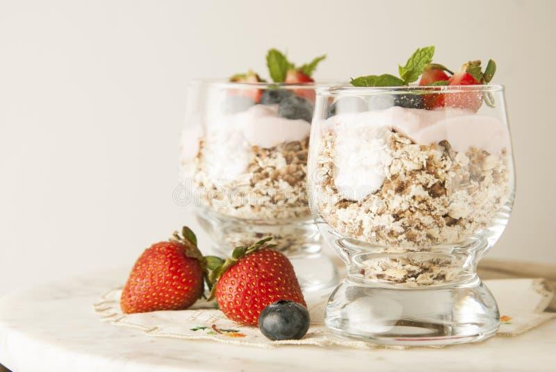健康早餐,燕麦膳食用果子:bluebery、strawbery和分钟,在一块玻璃的冷甜点在土气背景 健康的食物 免版税库存图片
