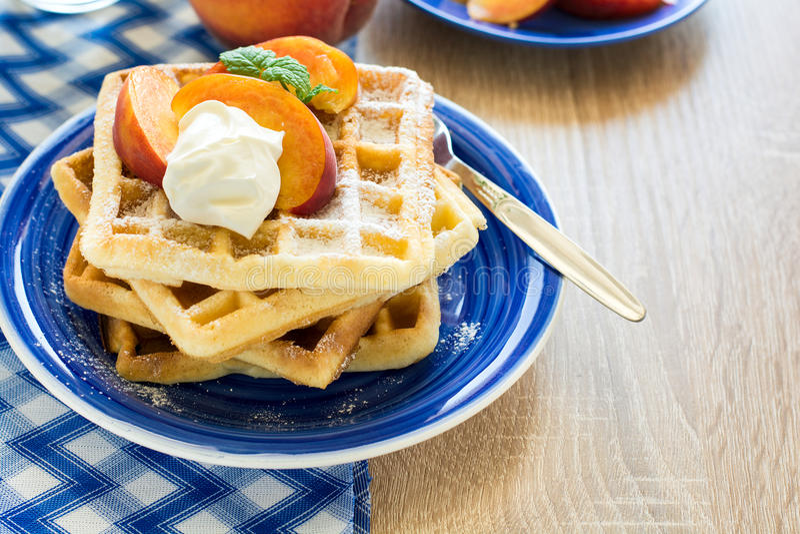 健康早餐:与桃子切片的比利时华夫饼干和奶油装饰了薄荷叶和蓝色餐巾 免版税库存图片