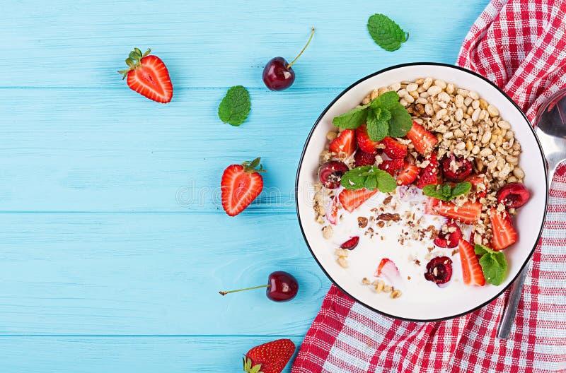 健康早餐-格兰诺拉麦片、草莓、樱桃、坚果和酸奶在一个碗在一张木桌上 库存图片