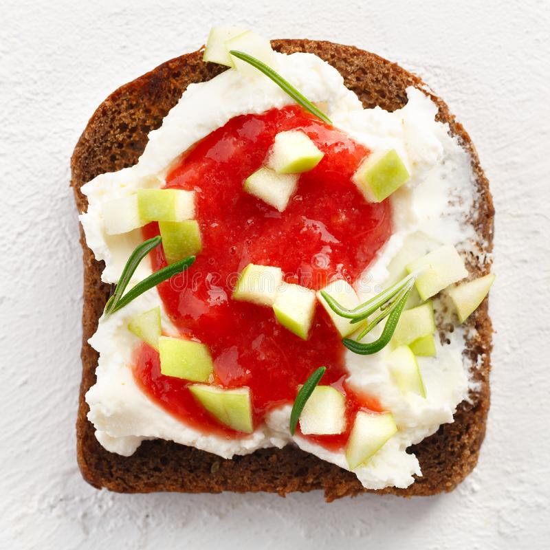 健康早餐Bruschetta用乳酪、草莓酱和苹果在白色背景 免版税库存图片