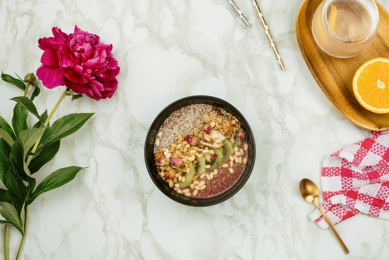 健康早餐Flatlay :素食主义者圆滑的人碗用chia布丁冠上与格兰诺拉麦片、猕猴桃、松果和玫瑰色芽 图库摄影
