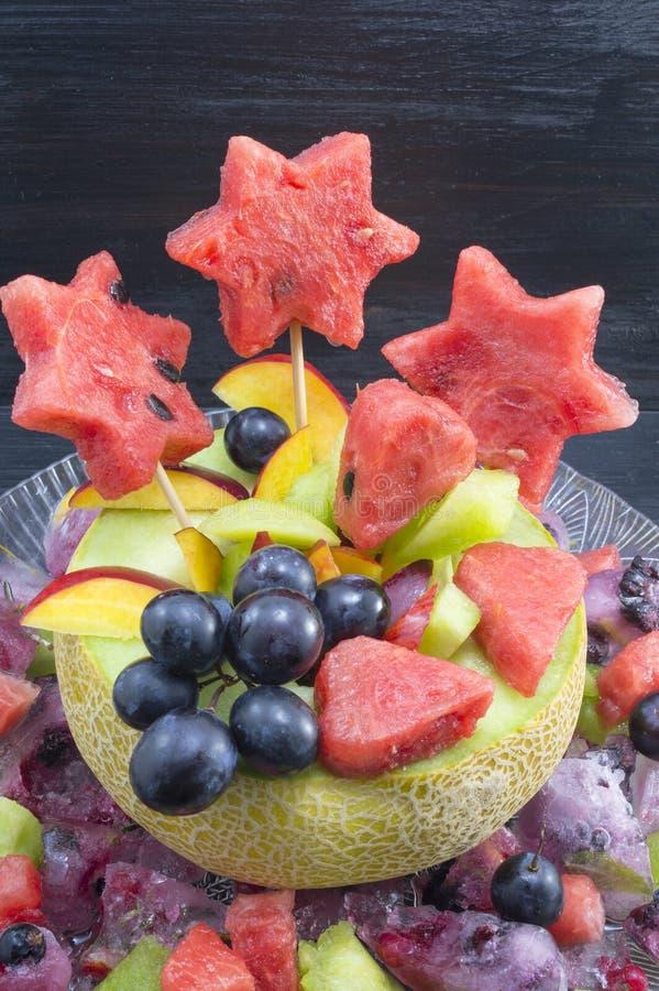 健康有吸引力的水果沙拉在一个新鲜的瓜服务反对b 免版税库存图片