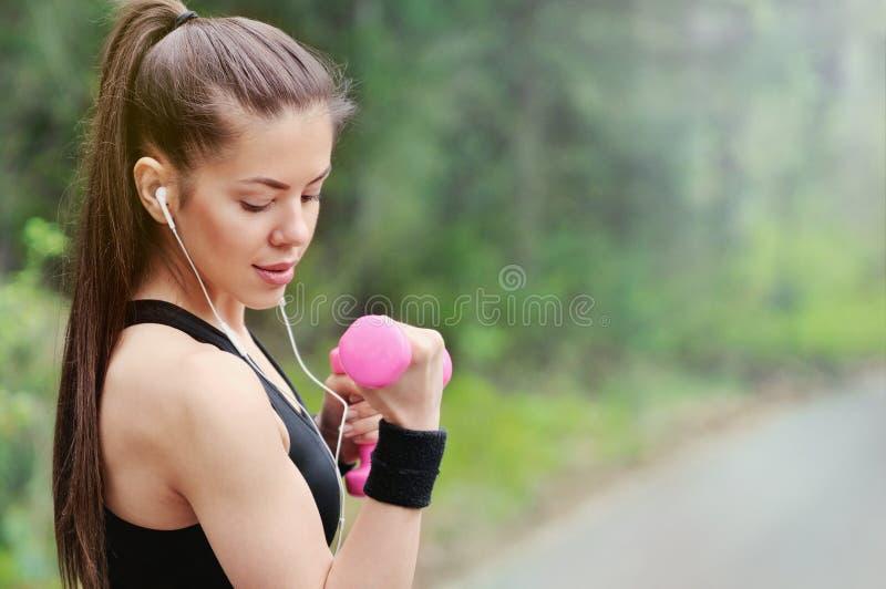 健康有哑铃和headpho的生活方式健身运动的妇女 免版税图库摄影