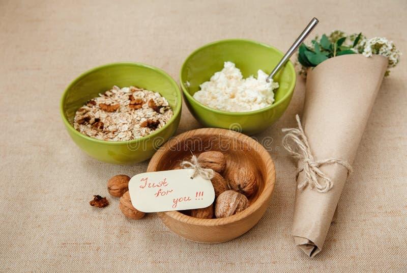 健康有机BreakfastWalnuts、燕麦粥和酸奶干酪的餐桌装饰品 绿色陶瓷和木板材 库存图片