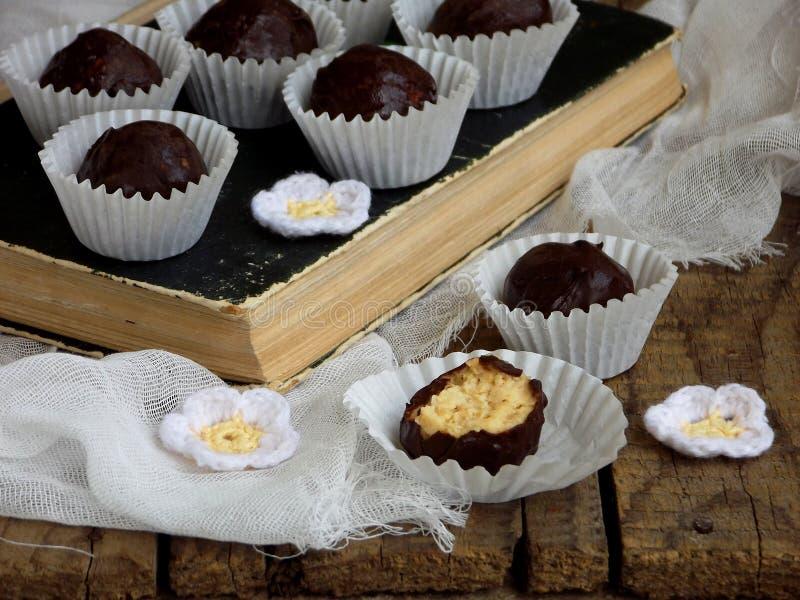 健康未加工的能量咬住用发芽的鸡豆、坚果和恶 用在木背景的巧克力盖的素食主义者块菌 Homema 免版税库存图片