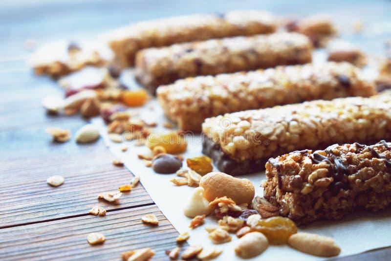 健康格兰诺拉麦片棒用干果子、坚果和蜂蜜在木背景 库存图片