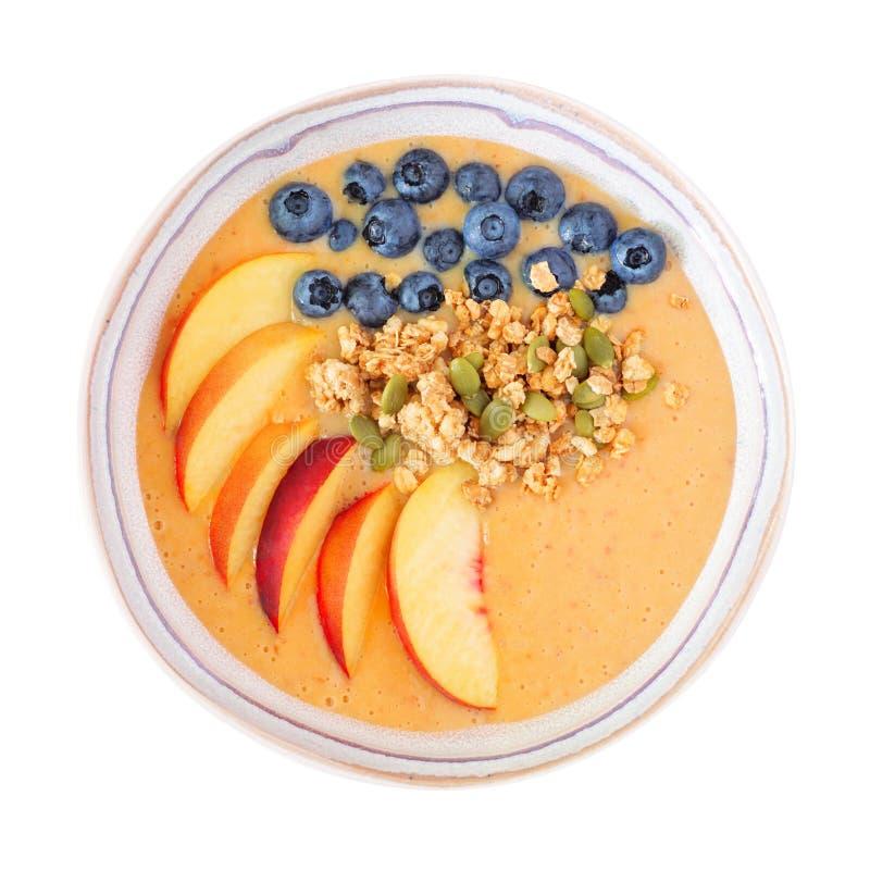 健康桃子圆滑的人碗用在白色和格兰诺拉麦片隔绝的蓝莓 库存图片
