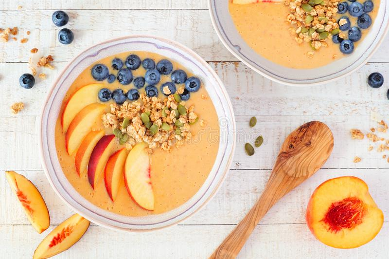 健康桃子圆滑的人碗用蓝莓和格兰诺拉麦片,顶视图在白色木头的桌场面 免版税库存图片
