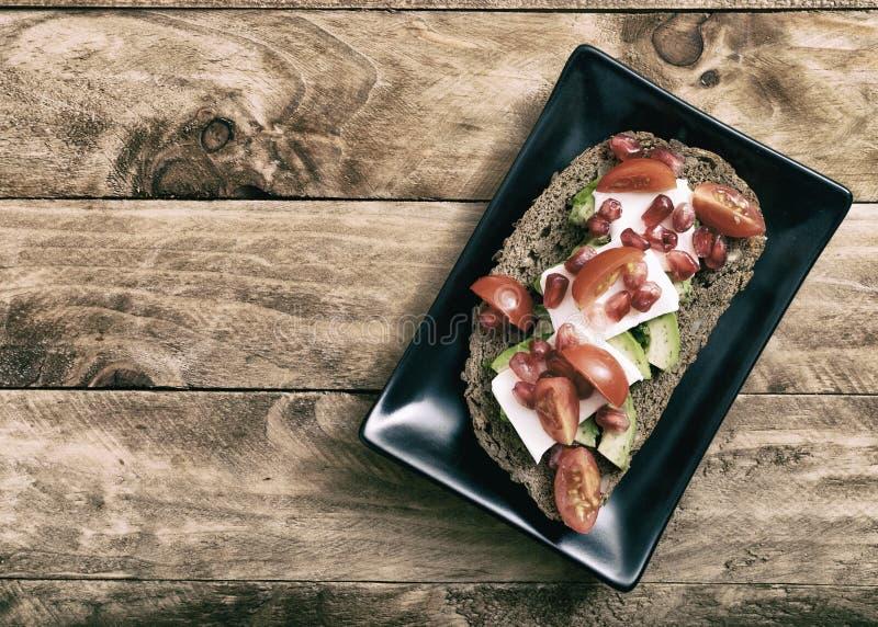 健康概念的食物 面包片用鲕梨、西红柿和新鲜的干酪 免版税库存照片