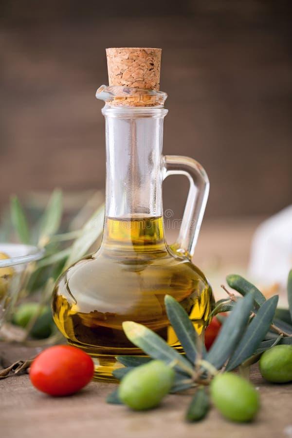 健康橄榄油和橄榄树枝在木桌上 免版税图库摄影