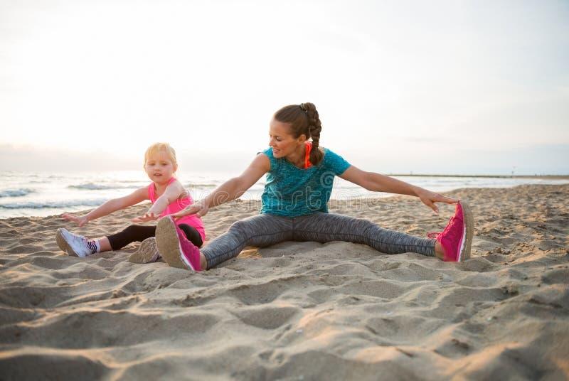健康母亲和舒展在海滩的女婴 免版税库存图片