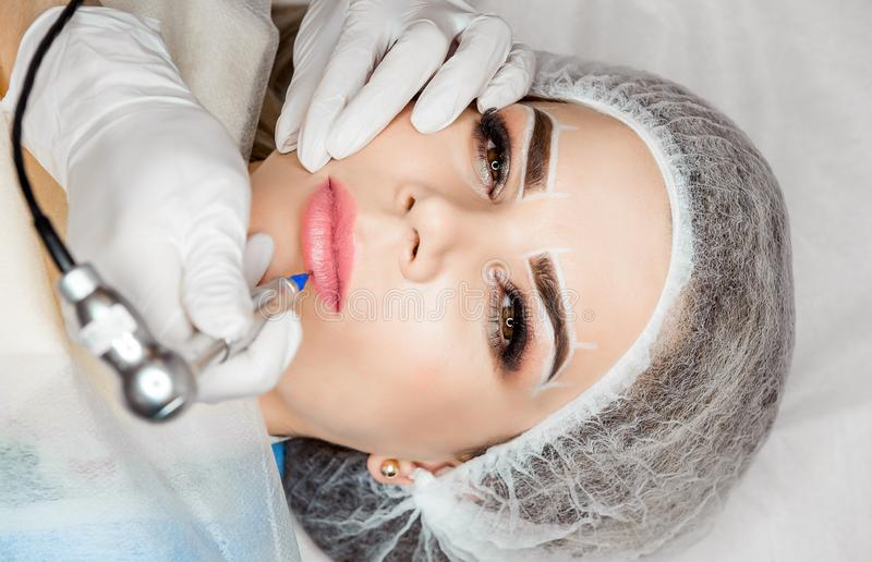 健康温泉 有年轻美丽的妇女在她的嘴唇的永久构成纹身花刺 免版税图库摄影