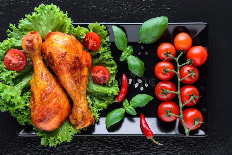 健康烤鸡腿用新鲜的蕃茄、basilik和辣椒在黑背景 免版税库存图片