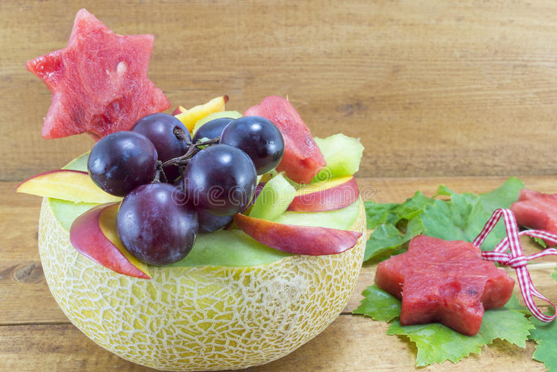 健康独特的水果沙拉在一张木桌上的一个新鲜的瓜服务 库存照片