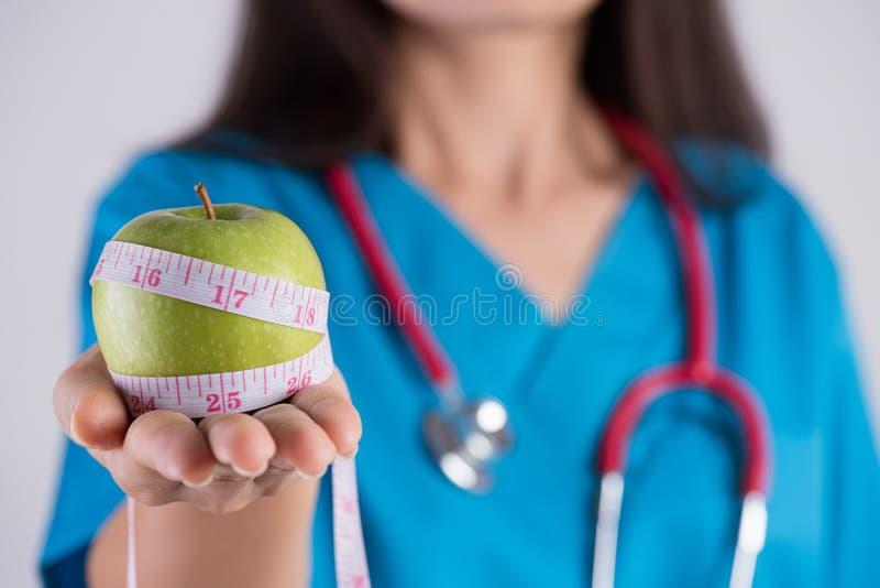 健康生活方式、食物和体育概念 拿着测量的磁带的微笑的医生妇女手的关闭在新鲜的绿色苹果附近 库存照片