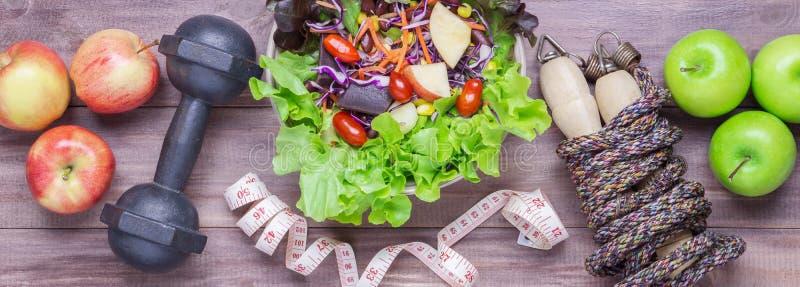 健康生活方式概念、运动器材和新鲜食品顶视图在木背景 万维网横幅 免版税库存图片