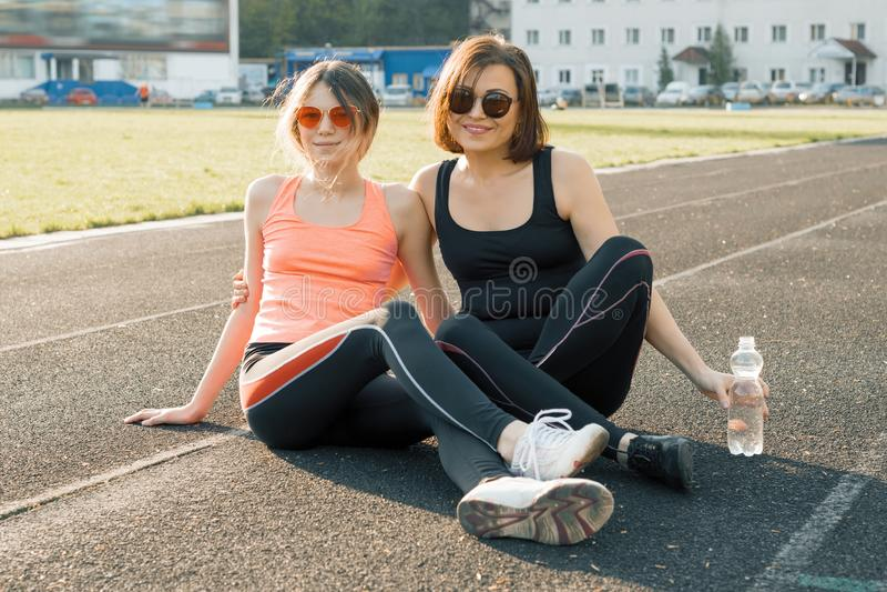 健康生活方式,健康家庭 一起摆在体育场的微笑的健身母亲和青少年女儿在跑在晴朗以后 库存照片