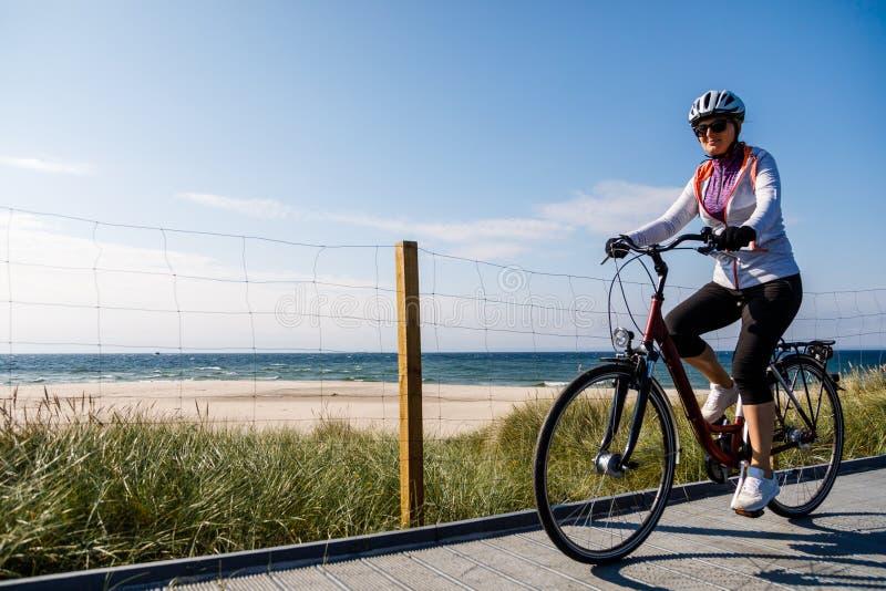 健康生活方式-中间年迈的妇女骑马骑自行车 库存图片