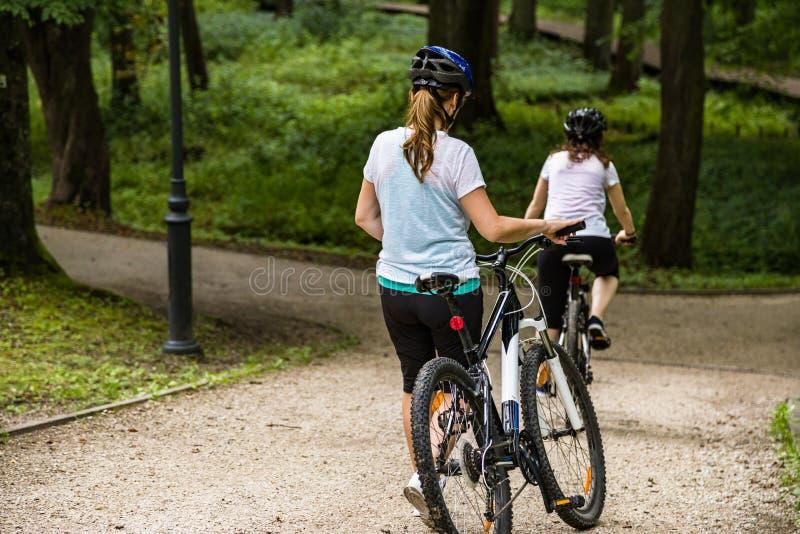 健康生活方式-人乘坐的自行车在城市公园 免版税库存图片