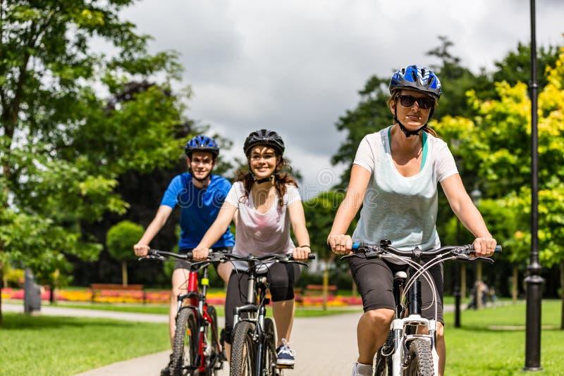 健康生活方式-人乘坐的自行车在城市公园 免版税库存照片