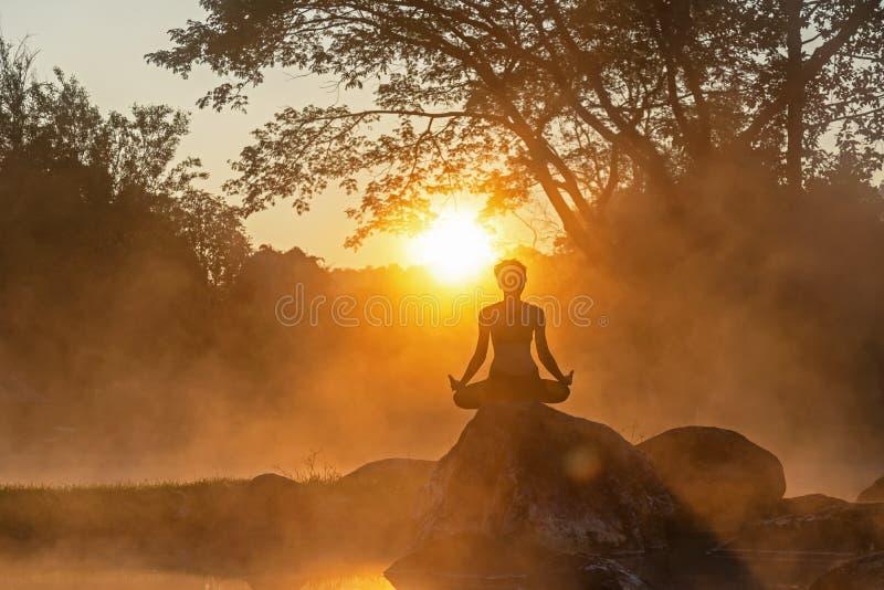 健康生活方式 早晨现出轮廓凝思瑜伽妇女为放松重要和能量 免版税库存照片