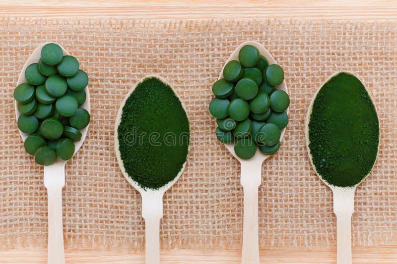 健康生活方式、superfood、海草、spirulina和小球藻药片和粉末在木匙子 库存照片