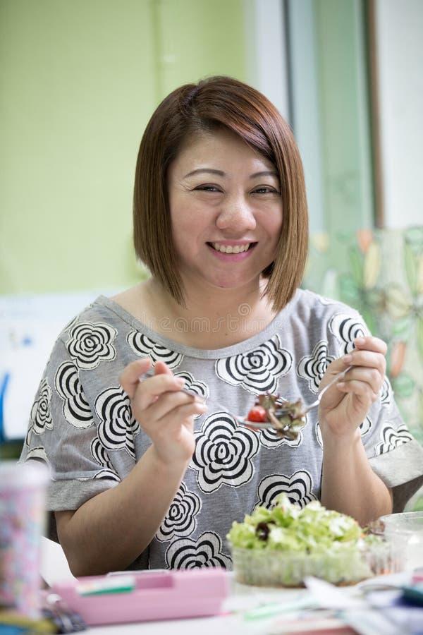 健康生活方式亚洲妇女吃沙拉微笑愉快在书桌上 库存照片