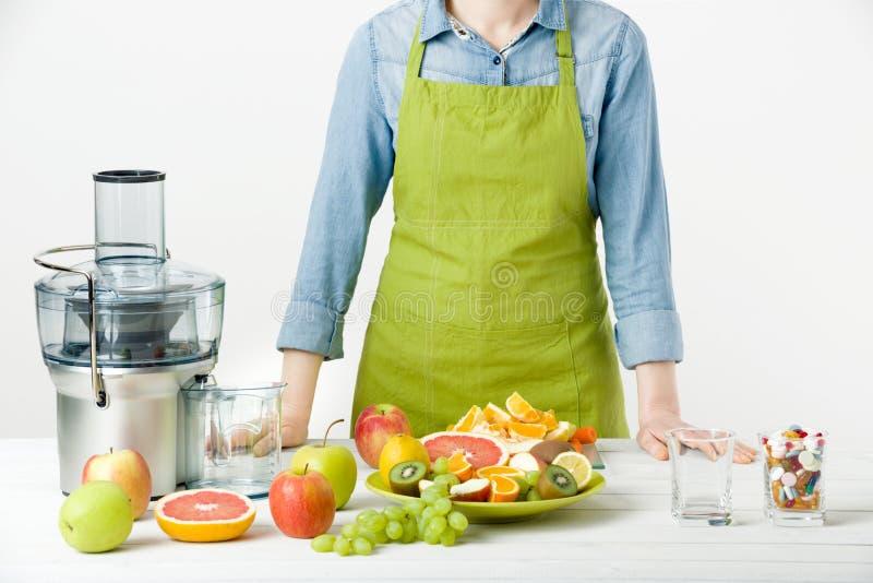 健康生活方式和饮食概念 果汁、药片和维生素补充,做出选择的妇女 免版税库存照片