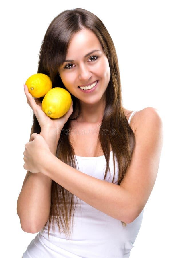 健康生活方式-美丽的俏丽的妇女拿着两个柠檬 图库摄影