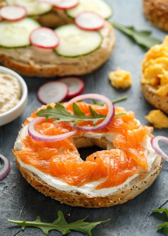 健康百吉卷用早餐与三文鱼、菜和奶油奶酪的三明治 免版税库存图片