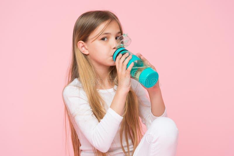健康的渴孩子饮料水在桃红色背景 儿童举行水瓶 有塑料瓶的小女孩 干渴和dehydr 免版税库存照片