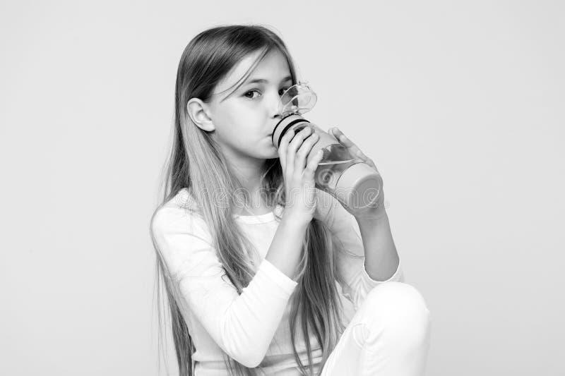 健康的渴孩子饮料水在桃红色背景 儿童举行水瓶 有塑料瓶的小女孩 干渴 免版税库存图片