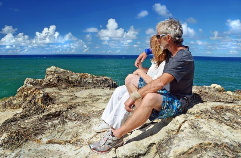 健康的老夫妇在登上悬崖顶热带岛屿后休息 免版税图库摄影