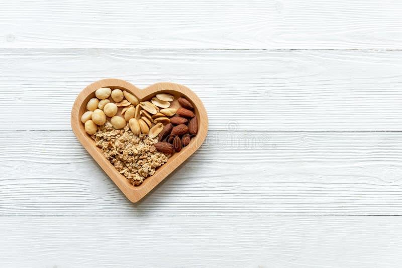健康的食物 在心形的混杂的坚果与饮食的坚果在白色木头 不同的种类鲜美和健康坚果 顶视图和 库存照片