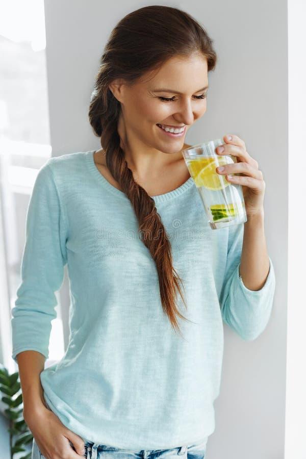 健康的食物 妇女饮用的柠檬戒毒所水 吃健康 免版税库存图片