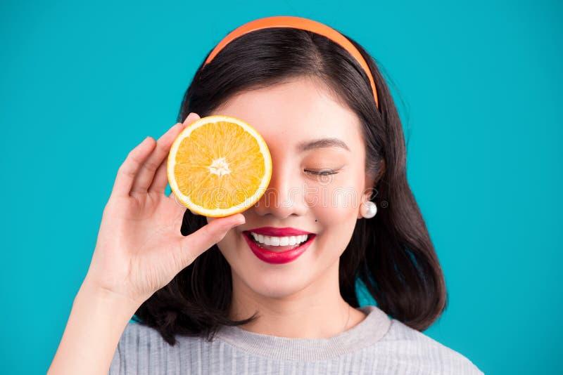 健康的食物 拿着橙色ove的微笑的可爱的画报亚裔女孩 免版税库存图片
