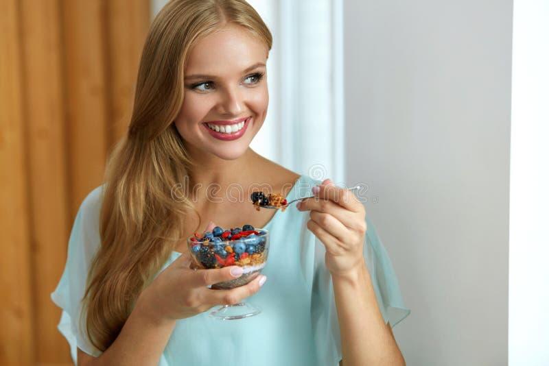 健康的饮食 吃谷物,莓果的妇女在早晨 营养 免版税库存图片