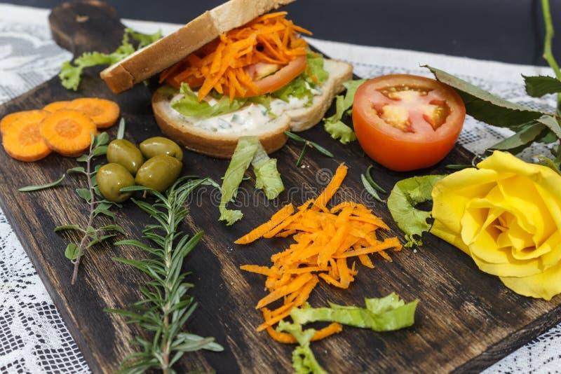 健康素食三明治用红萝卜,蕃茄,莴苣和香料,在一个木板服务,有一朵黄色玫瑰的 库存照片