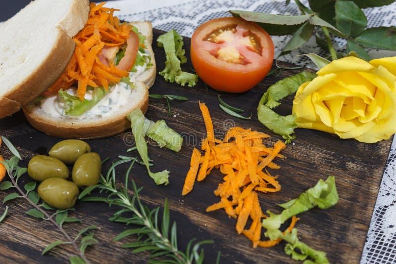 健康素食三明治用红萝卜,蕃茄,莴苣和香料,在一个木板服务,有一朵黄色玫瑰的 库存图片
