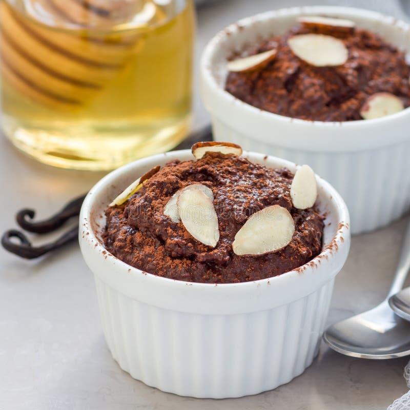健康素食主义者点心用鲕梨,可可粉、香草、蜂蜜和杏仁挤奶,巧克力沫丝淋,方形的格式 图库摄影