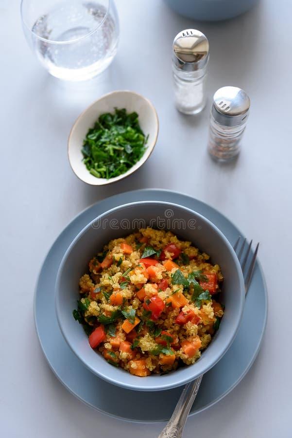 健康素食主义者碗用奎奴亚藜、南瓜、胡椒和红萝卜在灰色木背景 选择聚焦 免版税库存照片