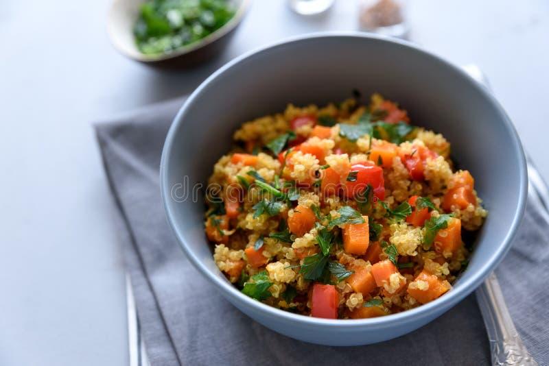 健康素食主义者碗用奎奴亚藜、南瓜、胡椒和红萝卜在灰色木背景 选择聚焦 图库摄影